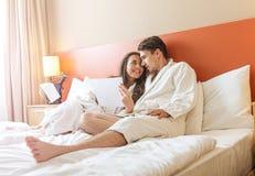 Jong Paar die in het bed van een hotelruimte liggen royalty-vrije stock foto's