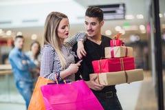 Jong paar die Kerstmis het winkelen doen stock foto