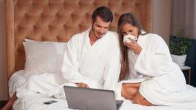 Jong paar die koffie in bed hebben terwijl het gebruiken van laptop stock videobeelden