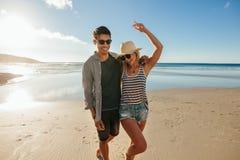 Jong paar die in liefde op het strand genieten van stock foto's