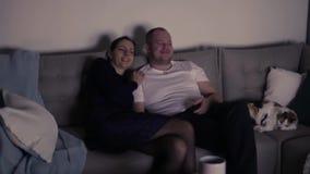 Jong paar die in liefde op TV letten bij nacht stock footage