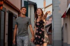 Jong paar die in liefde winkelvenster in een steeg in ascona tijdens zonsondergang bekijken stock afbeelding