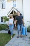 Jong paar die met bagage vanaf een huis lopen Stock Foto's