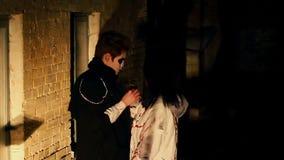 Jong paar die met enge make-up buitennachtclub, Halloween-partij koesteren stock footage