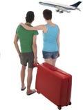 Jong paar die met koffer op vertraagd passagiersvliegtuig wachten Royalty-vrije Stock Foto's