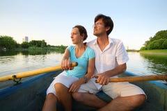 Jong paar die onderaan de rivier op een boot drijven Stock Afbeelding