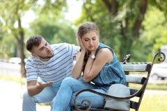 Jong paar die op bank in park debatteren Problemen in verhouding royalty-vrije stock afbeeldingen