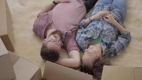 Jong paar die op de vloer met dozen dichtbij dichte omhooggaand liggen Man en vrouwenlach, die op pluizig tapijt liggen Gehuwd pa stock footage