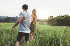 Jong paar die op een grasgebied wandelen Stock Afbeelding