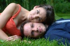 Jong paar die op het gras in een tuin leggen royalty-vrije stock fotografie