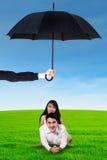 Jong paar die op het gras onder paraplu liggen Royalty-vrije Stock Afbeelding