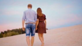 Jong paar die op het zand langs het strand lopen en handen houden bij zonsondergang stock video