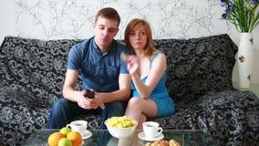 Jong paar die op TV op een bank thuis letten stock videobeelden