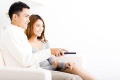 jong paar die op TV in woonkamer letten Stock Afbeeldingen
