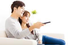 jong paar die op TV in woonkamer letten Stock Fotografie