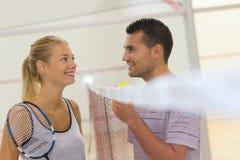 Jong paar die over netto badminton spreken stock afbeeldingen