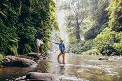 Jong paar die over stroom lopen Royalty-vrije Stock Afbeelding