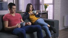 Jong paar die over TV-kanalen op bank debatteren stock footage