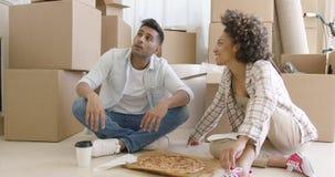 Jong paar die pizza en het babbelen eten stock video