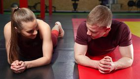 Jong paar die plankoefening doen die op de vloer in de gymnastiek liggen stock footage