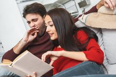 Jong paar die romantisch de lezingsboek hebben van de avond thuis vrouw stock afbeeldingen