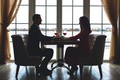 Jong paar die romantisch diner in de handen van de restaurantholding hebben royalty-vrije stock afbeeldingen