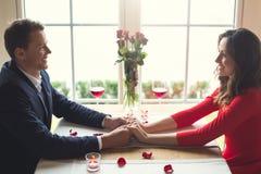 Jong paar die romantisch diner in de de holdingshanden hebben die van de restaurantzitting op elkaar kijken stock foto