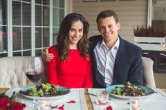 Jong paar die romantisch diner in de restaurantzitting die samen hebben camera kijken royalty-vrije stock foto
