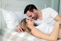 Jong paar die romantische tijd in slaapkamer hebben stock foto