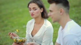 Jong paar die saladezitting op gras, picknick samen eten stock footage