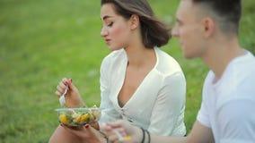 Jong paar die saladezitting op gras, picknick samen eten stock video
