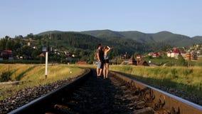 Jong paar die samen op oude spoorweg in bergen lopen stock video