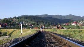 Jong paar die samen op spoorweg in bergen lopen stock footage