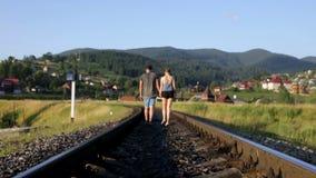 Jong paar die samen op spoorweg in bergen lopen stock video