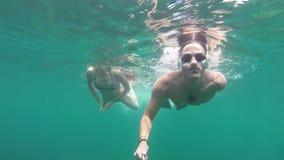 Jong paar die samen in open zee zwemmen stock footage