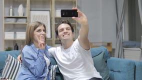 Jong Paar die Selfie met Smartphone nemen terwijl het Zitten op Laag stock videobeelden