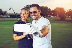 Jong paar die selfie op een golfcursus maken stock fotografie