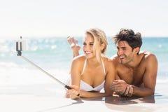 Jong paar die selfie op strand nemen stock afbeeldingen