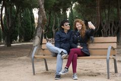 Jong paar die selfies bij het park op een winter& x27 nemen; s dag Stock Fotografie