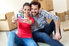 Jong paar die selfies in hun nieuw huis nemen Stock Afbeelding