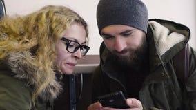 Jong paar die smartphonezitting in koffie in stad gebruiken stock video
