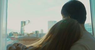 Jong paar die stads van mening genieten door het venster stock footage