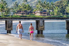 Jong paar die strand, Kauai, Hawaï wandelen stock foto
