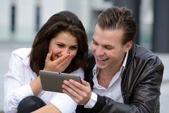 Jong paar die tablet gebruiken stock foto