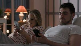 Jong paar die telefoon met Internet in slaapkamer met behulp van stock video
