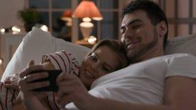 Jong paar die telefoon met Internet in slaapkamer met behulp van stock videobeelden