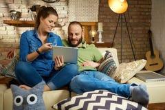 Jong paar die thuis tablet gebruiken Stock Foto
