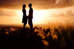 Jong paar die van de zonsondergang genieten royalty-vrije stock foto's
