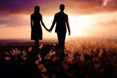 Jong paar die van de zonsondergang genieten stock afbeeldingen