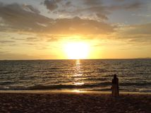 Jong paar die van de zonsondergang op het strand genieten Stock Afbeelding